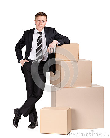 Manager stands near pile of pasteboard boxes