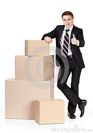 Manager in suit stands near pile of containers