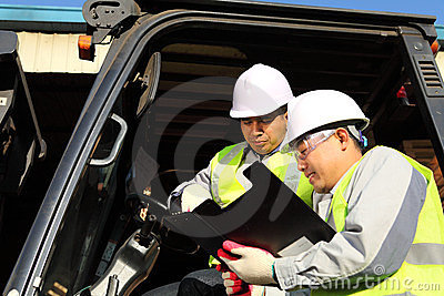 Manager talking to forklift operator