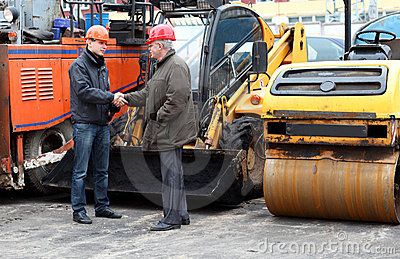 Managers of works in hard hats shaking hands