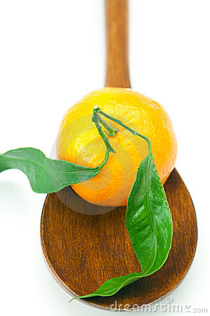 Mandarin with green leaves on a wooden spoon