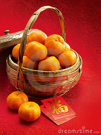 Mandarins in a basket and red packets in red clot