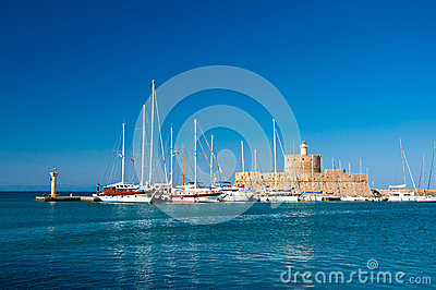 Mandraki harbor and the old lighthouse. Rodes, Greece.