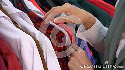 Mani della donna che cercano blusa casuale in boutique archivi video