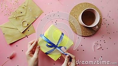 Mani di donna che cercano di aprire un regalo di Natale avvolte in un foglio giallo con arco blu Vista dall'alto sulla tavola ros video d archivio