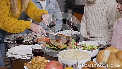 Mani di donne che usano forchetta e coltello per tagliare il tacchino arrosto durante la cena di famiglia stock footage