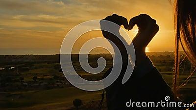 Mani femminili nella forma di cuore contro il tramonto video d archivio