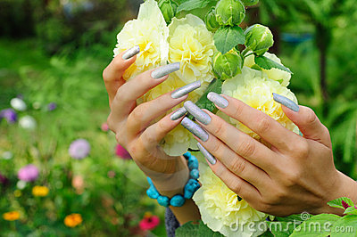 Manicure on real nails and yellow hollyhock flower
