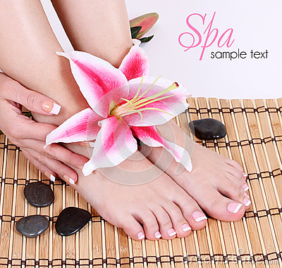 Manicured female bare feet with pink lily flower and spa stones over bamboo mat