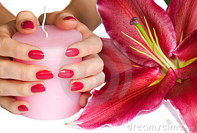 Manicured hands holding candle