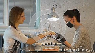Manicurist смотрит ногти ` s девушки на протягивать машину видеоматериал