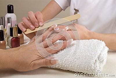 Manicurist filing womans nails