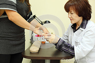 Manicurist looks at customer nails