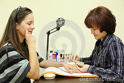 Manicurist makes manicure by nailfile for woman