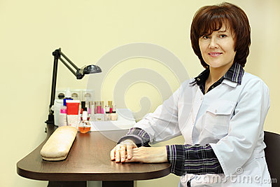 Manicurist sits at table for manicure