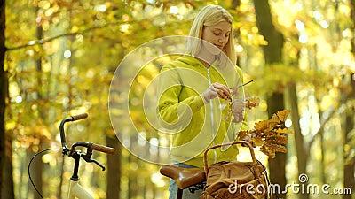 Manillar viejo de la bici de la tenencia de brazos de las muchachas con la cesta de las flores Viaje al aire libre de las vacacio metrajes