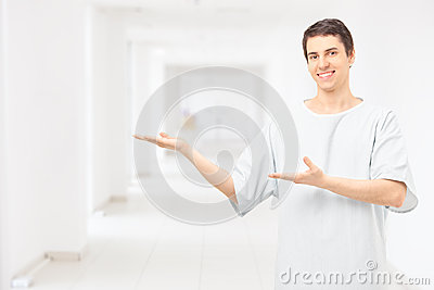 Manlig tålmodig bärande sjukhuskappa och göra en gest med händer i a