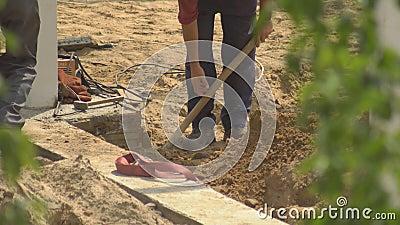 Manliga arbetare gräver ett hål med en skiva på en byggarbetsplats under uppförandet av en byggnad, ett manuellt arbete, en indus lager videofilmer