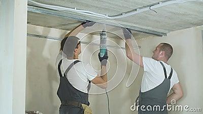 Manliga byggmästare som inomhus använder för metalldrywall för elektrisk drillborr monterande profiler på konstruktionsplats lager videofilmer