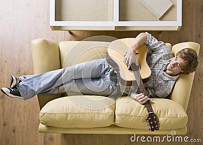 Mann, der auf das Sofa spielt Gitarre legt