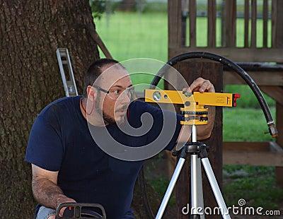 Mann, der Laser-Stufe verwendet