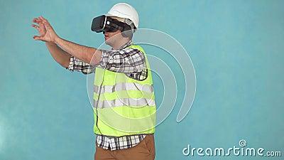 Mann in einem Sturzhelm und in einer Uniform benutzt einen VR-Sturzhelm stock footage