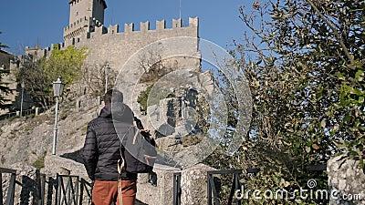 Mann geht nahe mittelalterlichem Schloss in der Tageszeit stock video footage