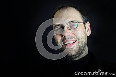 Mann mit Gläsern und Bart, die im Schwarzen lachen