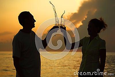 Mann und Frau klirren Gläser. Spritzt vom Wein.
