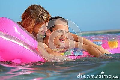 Mann und Frauen, die auf einer aufblasbaren Matratze liegen