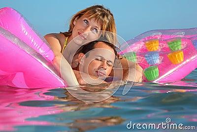 Mann und Frauen, die auf einer Matratze im Pool liegen