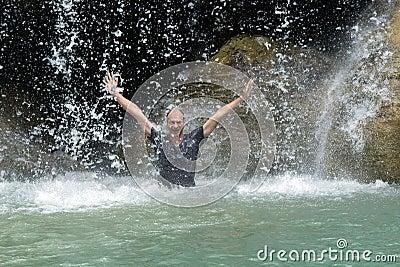 Mann unter Wasserfallfluß