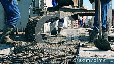 Mannelijke bouwbedrijven gieten nat beton op een vloer terwijl ze werken op een bouwplaats stock video