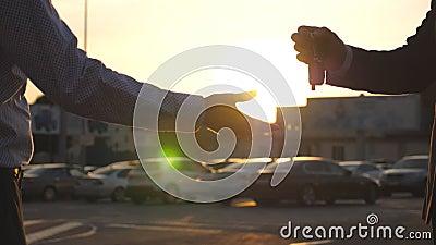 Mannelijke handen die van handelaar sleutels van auto geven aan cliënt met zongloed bij achtergrond Wapen van zakenman overgegaan stock videobeelden