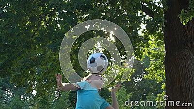 Mannelijke jongen speelt bal in de tuin, met kop, kindersportclub, activiteit stock footage
