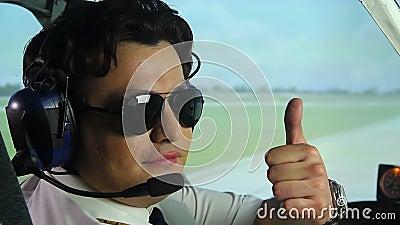 Mannelijke proef genietend van zijn werk, zittend in cockpit van lijnvliegtuig, het tonen beduimelt omhoog stock video