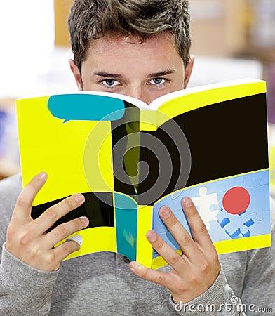 Mannelijke student die zijn gezicht achter een boek verbergt