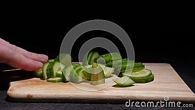 Mannelijke vingers verplaatsen gesneden komkommerplakken op een donkere achtergrond stock footage