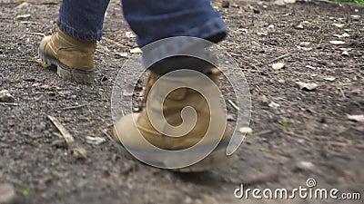Mannelijke voet in schoenen die op de achtermening van de plattelandsweg lopen Mens die in schoenen van beige leer op voetpad, la stock footage