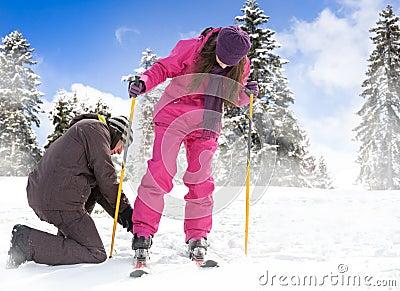 Mannen hjälper hennes flickvän att sätta henne skidar