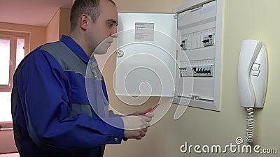 Mannen med skruvmejsel vänder på utklipp och stänger paneldörren lager videofilmer