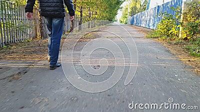 Mannen promenerar asfalten stock video