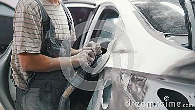 Mannmechanikerpolituren gemalt in einer silbernen Fahrzeugkarosserie mit einem Schleifer stock footage
