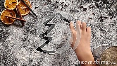 Mano del bambino che disegna un albero di Natale nella farina