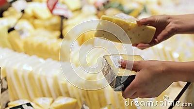 Mano del compratore con un pezzo di formaggio nel deposito archivi video
