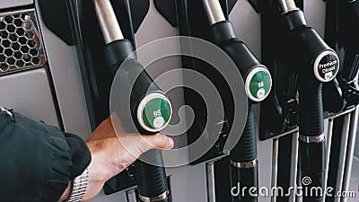Mano del hombre tomando el inyector de combustible en la gasolinera almacen de video