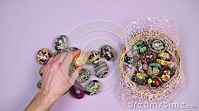 Mano di uova di Pasqua sulla tavola vicino al cestino su fondo rosa La Pasqua è santa 4k video d archivio