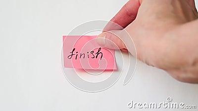 Mano pega una pegatina en un fondo blanco con el texto escrito a mano `Finalizar' almacen de video