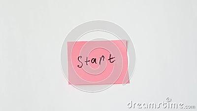 Mano pega una pegatina en un fondo blanco con el texto manuscrito 'Inicio' almacen de metraje de vídeo