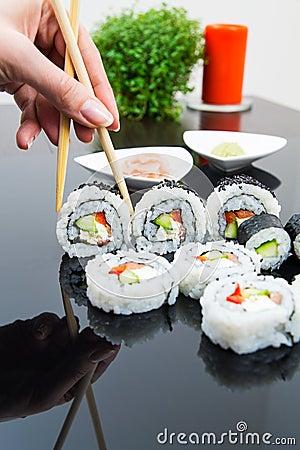 Mano que sostiene el palillo con el conjunto del sushi del maki